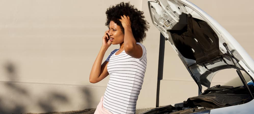 Woman calling for assistance standing near broken down car