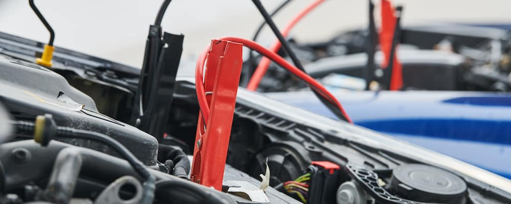 A set of jumper cables connecting two vehicles and charging a dead battery.