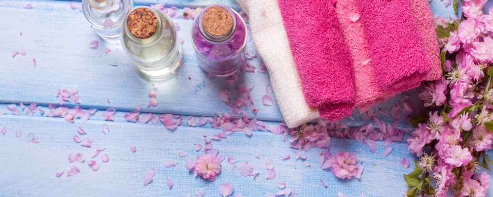 A few bottles of essential oil next to a towel, with flower petals strewn about.
