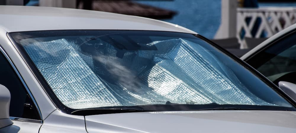 Reflective sunshade in front windshield of car