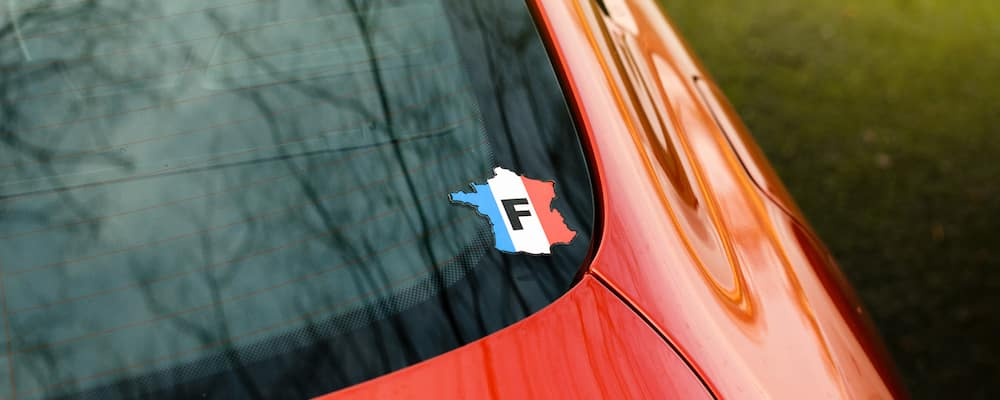 "Closeup of ""F"" (for France) sticker on windshield of red car"