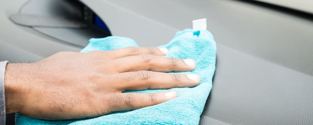 Person wiping dashboard with blue cloth
