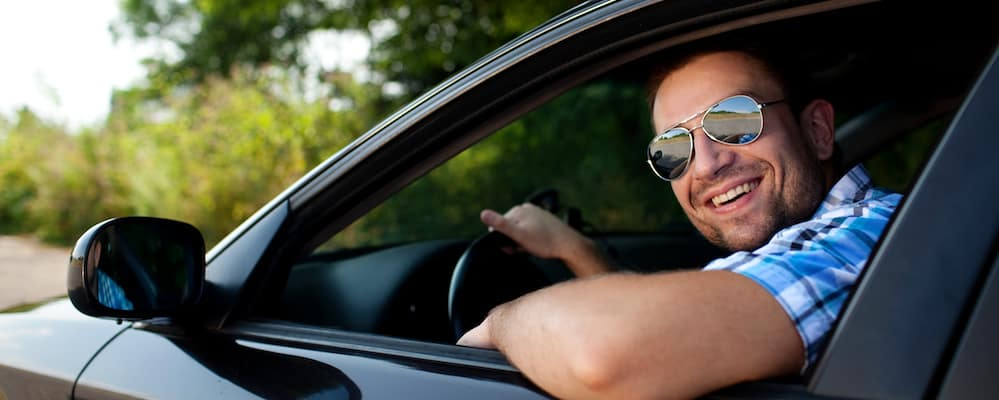Smiling man wearing sunglasses driving a car