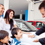 Happy family with the dealer buying a new car