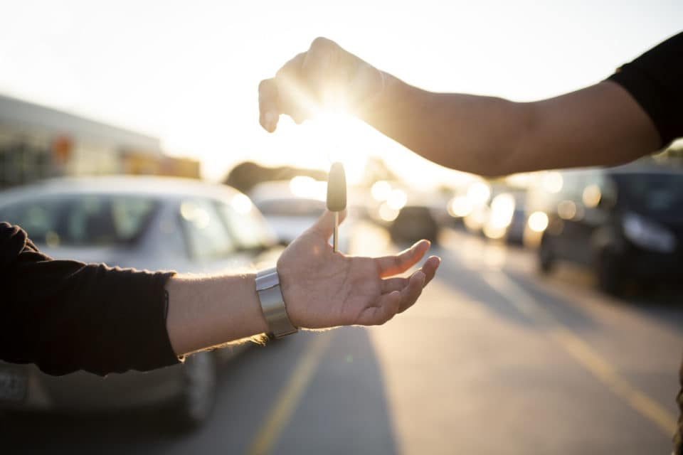 Car Key in Human Hand giving to another hand in a car lot