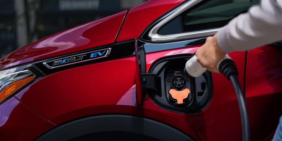 A person charging a red 2020 Chevrolet Bolt EV - El Dorado Chevrolet in McKinney, Texas