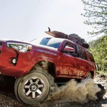 Red Toyota 4Runner side view driving out of woods