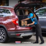 Amazon delivery driver loading a package into a customer's vehicle