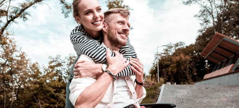 Woman smiling and hugging smiling boyfriend in wheelchair