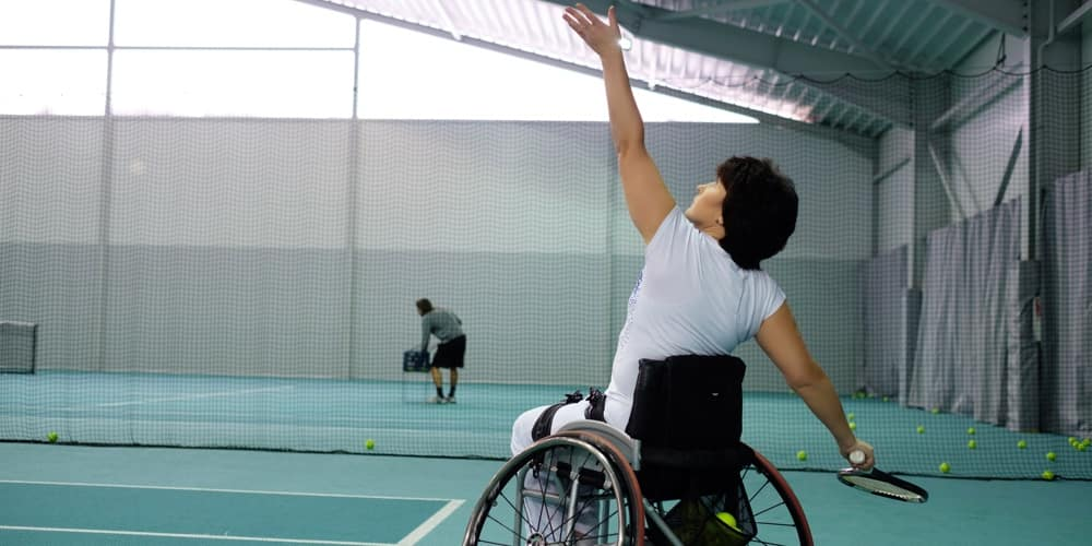 Mature woman on wheelchair playing tennis on tennis court.