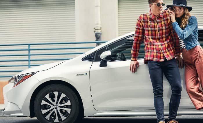 2020 Toyota Corolla with couple leaning against door