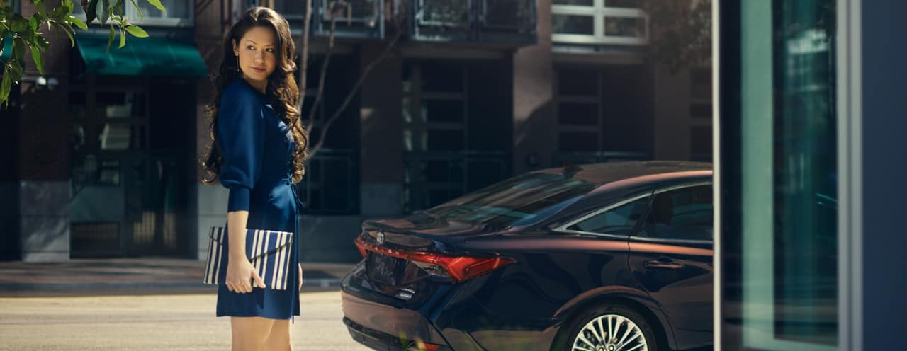 woman stands near rear of Toyota Avalon