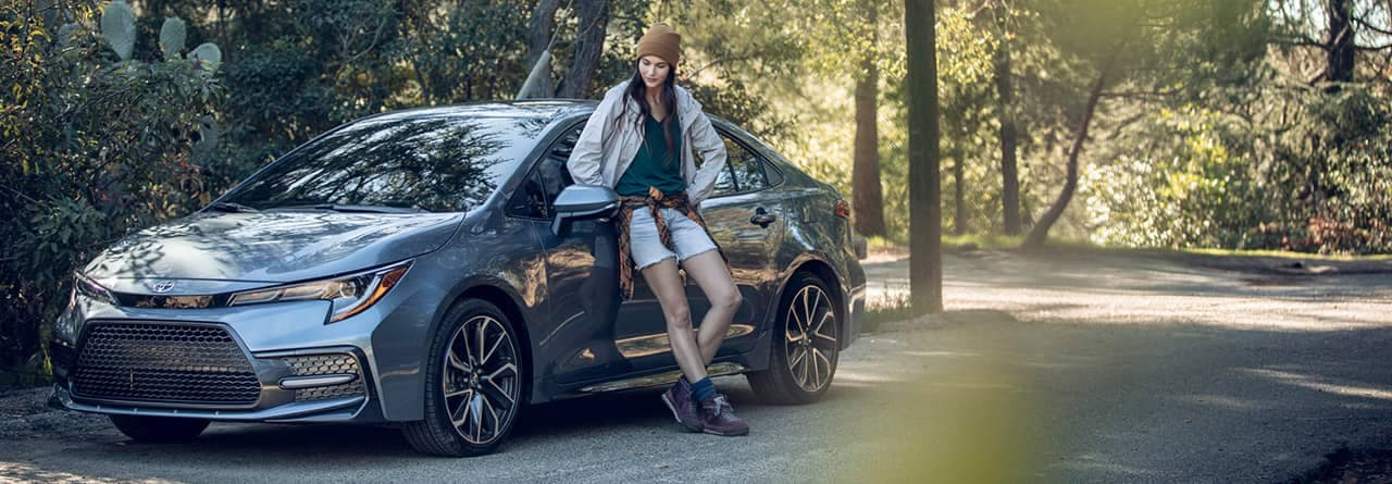 young woman leans against toyota