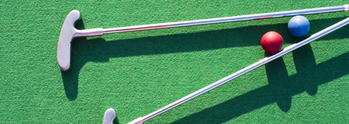 close up of mini golf clubs and mini golf balls on green