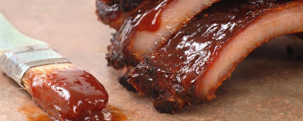 Close on bbq ribs with bbq brush