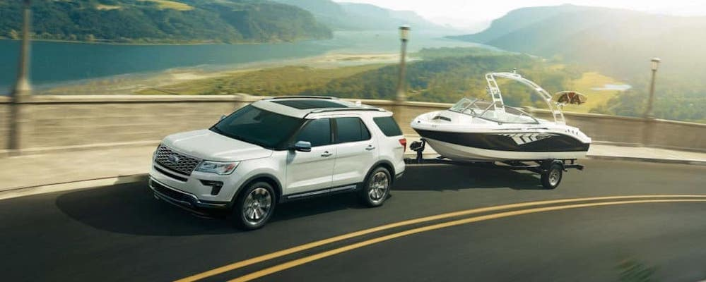 White Ford Explorer towing boat on mountain highway