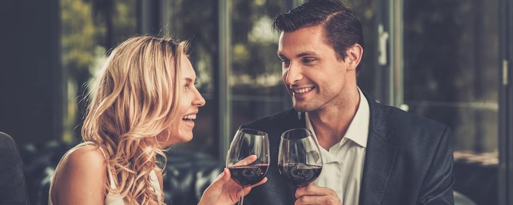 Handsome young couple sipping wine together at a fine dining restaurant.