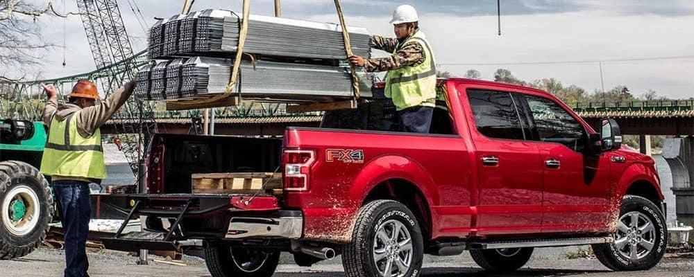 Workers loading steel beams in red Ford F-150