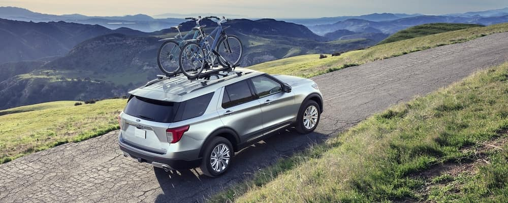 Silver 2020 Ford Explorer driving up mountain with two bikes on roof rack