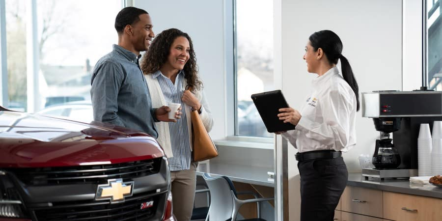 A man and woman interacting with a female employee at a Chevrolet dealership - Graff Chevrolet in Grand Prairie, Texas
