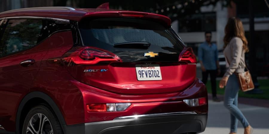 A woman and man standing near a red 2020 Chevrolet Bolt EV - Graff Chevrolet in Grand Prairie, Texas