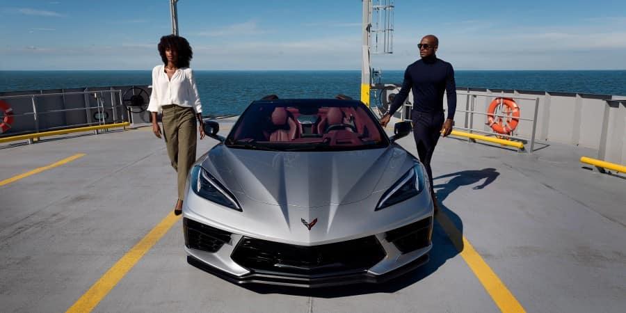 A man and woman next to a silver 2021 Chevrolet Corvette - Graff Chevrolet in Grand Prairie, Texas