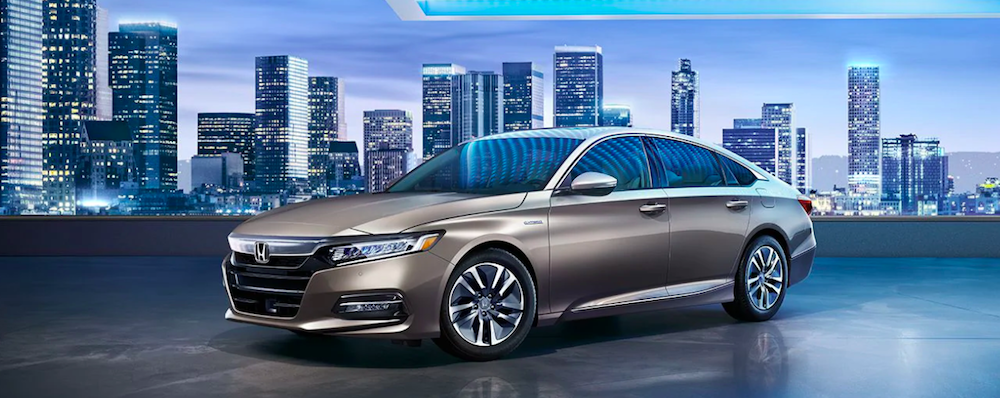 A 2020 Honda Accord parked in front of a city skyline
