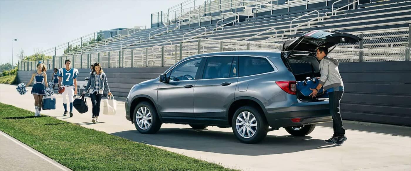 Family loading up a 2021 Honda Pilot after a football game