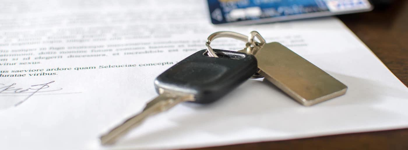 car keys and a credit card on top of a signed loan