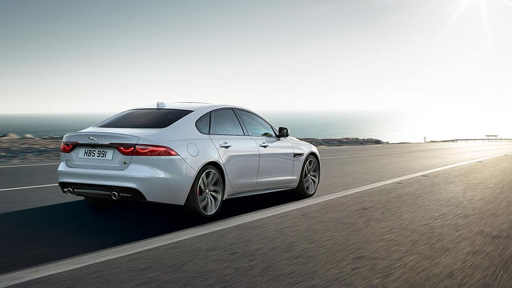 2019 Jaguar XF driving towards sunset