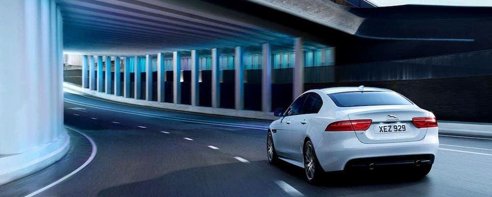 2019 Jaguar XE in white driving under bridge