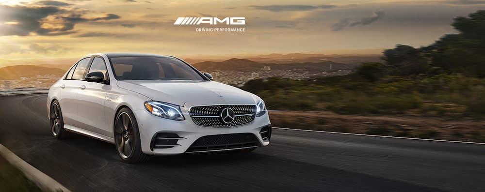 white mercedes-benz amg sedan speeding down highway