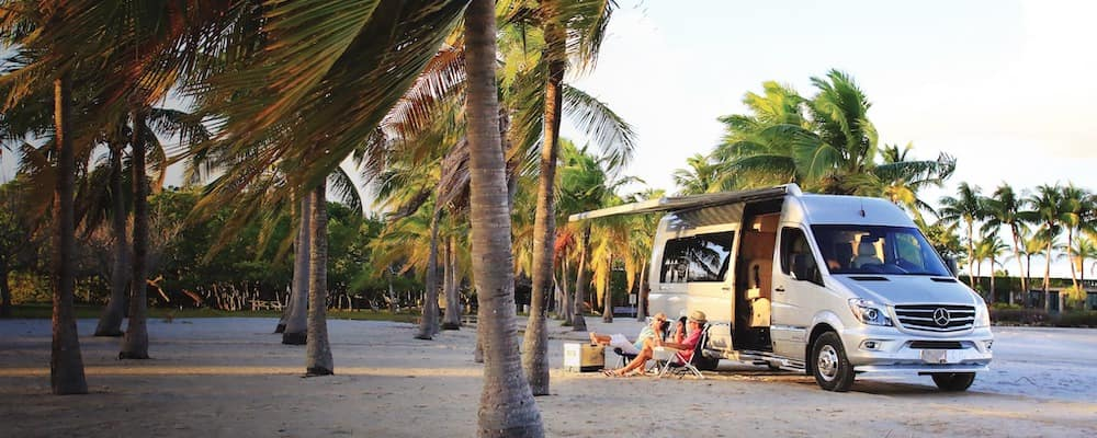 Exterior of Mercedes-Benz Airstream Tommy Bahama Relax Edition open on beach with campers
