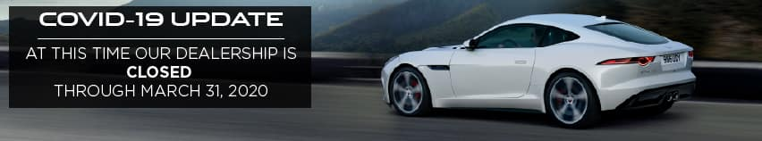 COVID-19 UPDATE. AT THIS TIME OUR DEALERSHIP IS CURRENTLY CLOSED THROUGH MARCH 31, 2020. WHITE JAGUAR F-TYPE COUPE DRIVING DOWN ROAD NEAR MOUNTAIN.