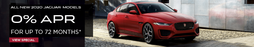 ALL NEW 2020 LAND ROVER MODELS. 0% APR. FOR UP TO 72 MONTHS. VIEW SPECIAL. RED JAGUAR XE DRIVING DOWN ROAD IN CITY.