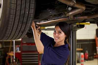 Female auto mechanic checking car tire