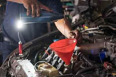 Mechanic adding engine oil to car
