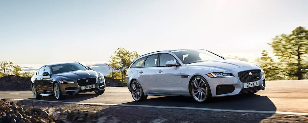 Two 2019 Jaguar XF models driving on seaside highway
