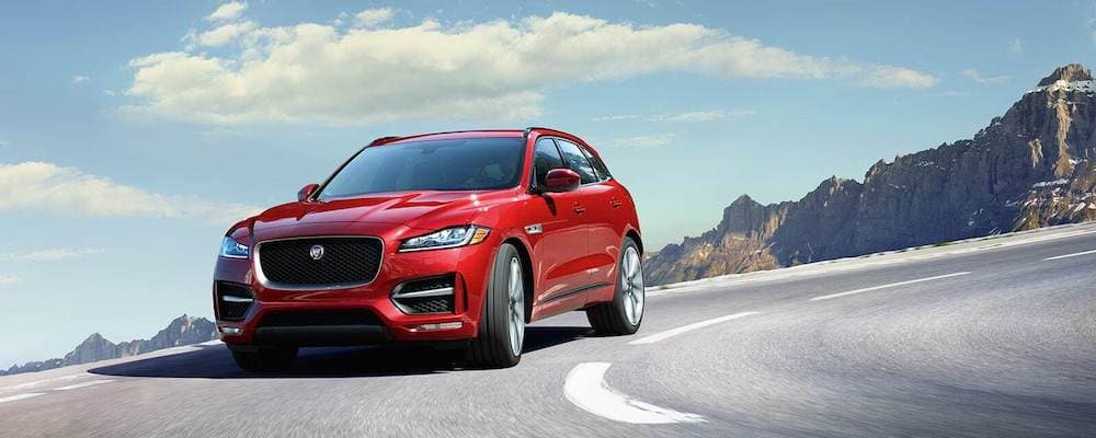 2019 Red Jaguar F-PACE in red driving on open highway