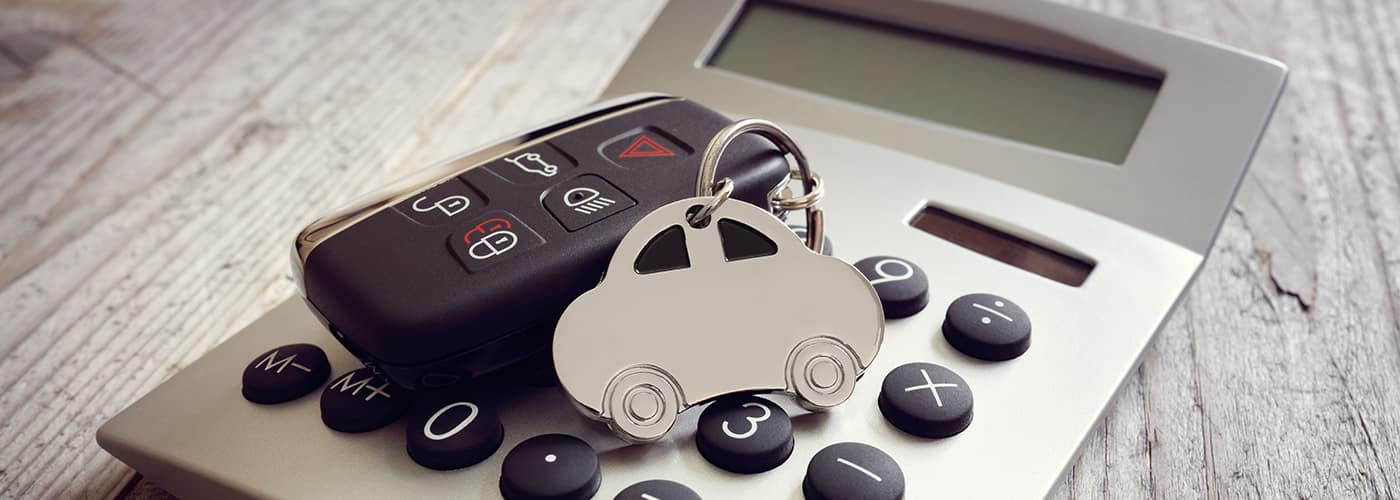 Car shape keyring and key on calculator concept for motoring costs, finance, insurance, servicing or fuel bills