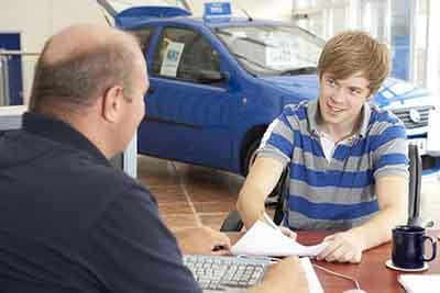 Young man filling in paperwork in car showroom