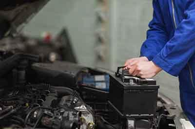 Male mechanic changing car battery