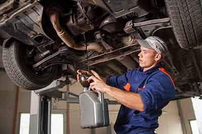 Mechanic draiging car oil