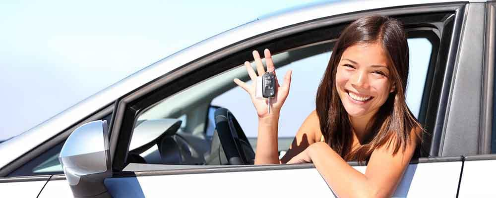 Woman holding car keys in the drivers seat