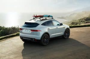 2019 Jaguar E-PACE Driving Along Ocean with Surf Board on Roof Rails