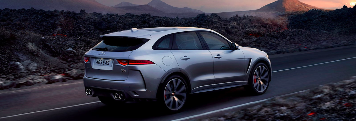 Back View of Jaguar SUV driving on a road in front of mountains