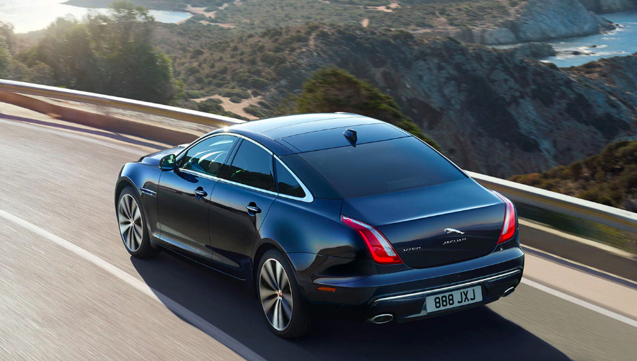 Back view of black Jaguar XJ driving on winding road