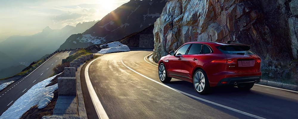 Red Jaguar F-PACE driving along mountain side road