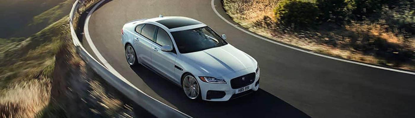silver jaguar xf driving on curvy mountain road