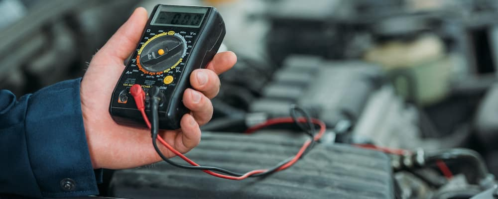 Auto mechanic using digital multimeter